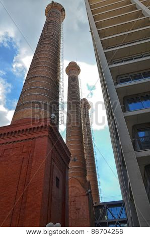 Abandoned Smokestack In Urban Panorama