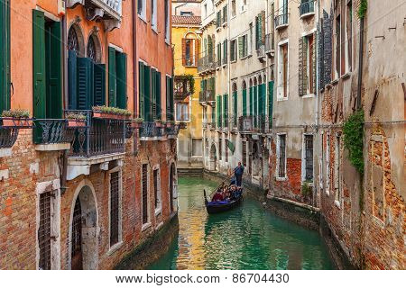 VENICE, ITALY - NOVEMBER 13, 2012: Gondola on small canal among old houses in Venice - one of the most beautiful cities and popular destinations in the world with an average of 50,000 tourists a day.