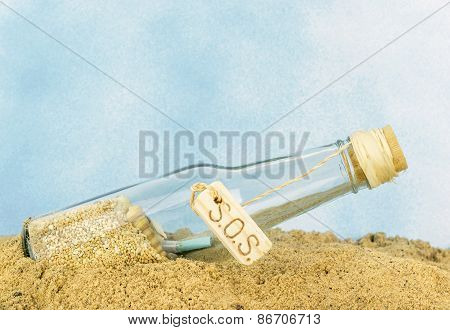 A glass bottle with SOS in sand