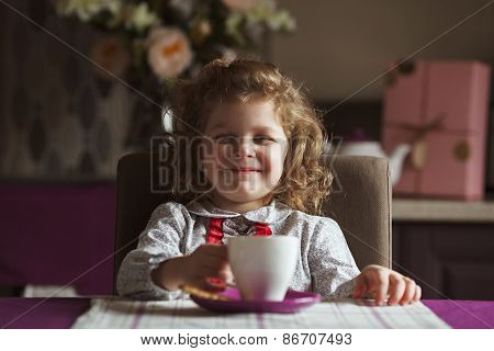 Cheerful Girl Sitting At The Table