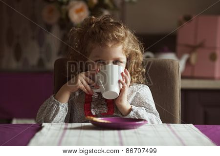 Little Girl Drinking From A White Cup