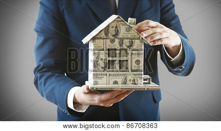 Model of house made of money in male hands on gray background
