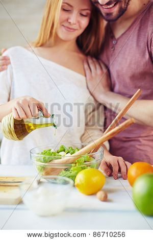 Young woman seasoning salad with olive oil