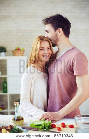 Happy and amorous dates standing by table with vegetarian food