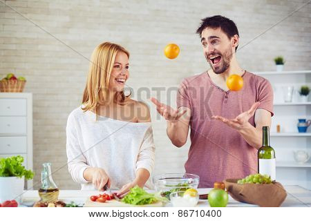 Happy young woman cooking salad in the kitchen, handsome man juggling oranges near by