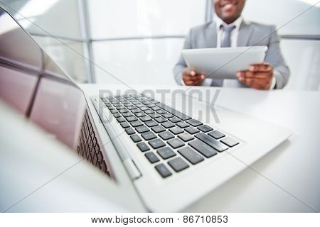 Keypad of open laptop and businessman with touchpad on background