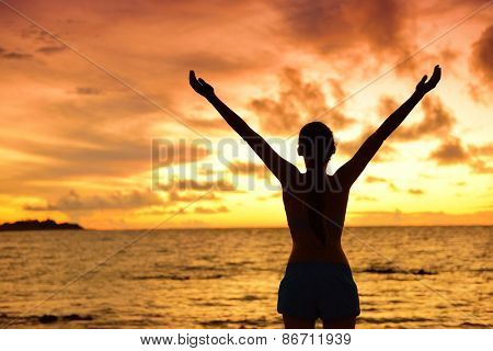 Freedom woman silhouette living healthy lifestyle a happy carefree and free life. Portrait from the back of an unrecognizable female adult at beach holidays in sunset with arms raised up in the sky.