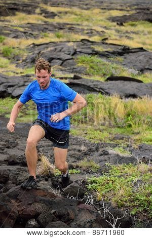 Active man trail running on volcanic rocks in mountain background. Male athlete racing doing an ultra marathon through rugged landscape in Hawaii, USA.