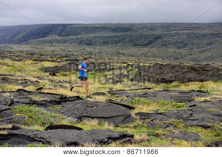 Runner. Sport running man in cross country trail run. Male athlete exercising and training outdoors in beautiful mountain nature landscape.