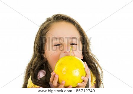 Adorable healthy little girl eating a passionfruit in front of her face