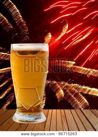 Beer Glass On Wooden Table Against Of Multicolored Fireworks.