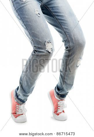Human legs in jeans and shoes isolated on white