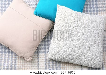 Decorative pillows on plaid close up