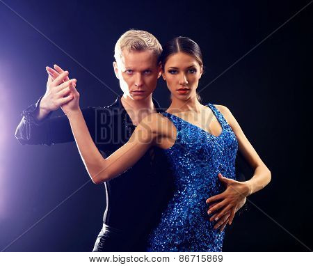 Beautiful couple of professional artists dancing on black background