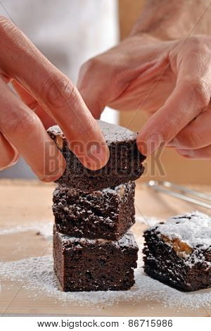 Pastry chef hands preparing and slicing fresh chocolate brownies on cutting board.