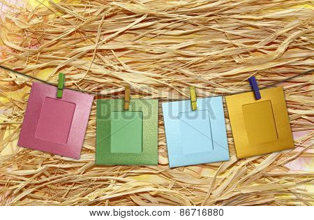 Colorful Paper Frame With Clothespins On A Straw Background