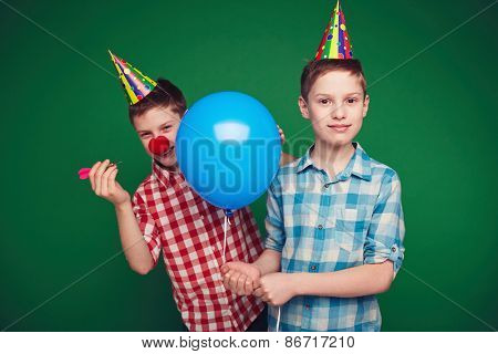 Sly boy in birthday cap going to burst balloon of his brother