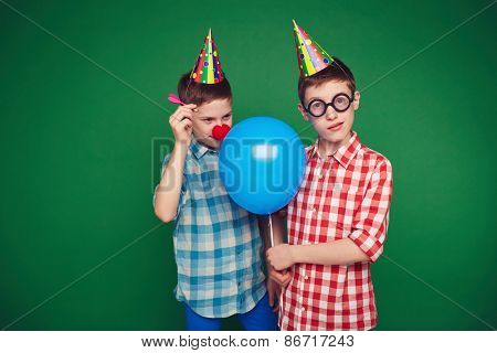 Goofy child going to burst balloon of his brother