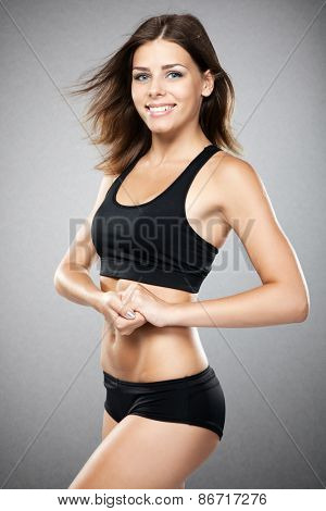 Young fit woman in sports outfit, studio photo