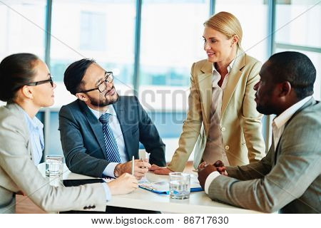 Happy businesswoman explaining her idea to employees at meeting