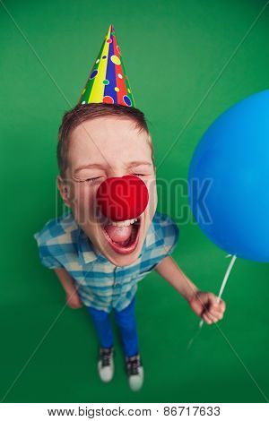 Goofy boy with balloon and clown nose shouting at foolâ??s day celebration