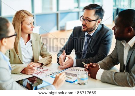 Serious businessman explaining principles of work to his colleagues at meeting