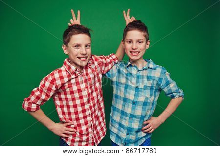 Smiling twins making fun of one another