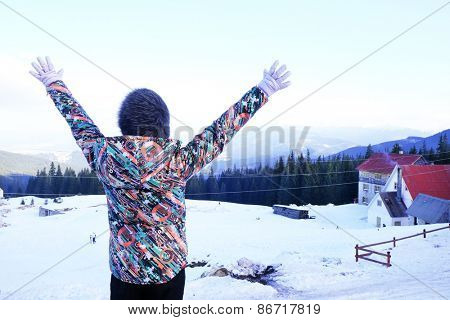 Woman in warm clothing turned back raising her hands up over Carpathian Mountains in wintertime