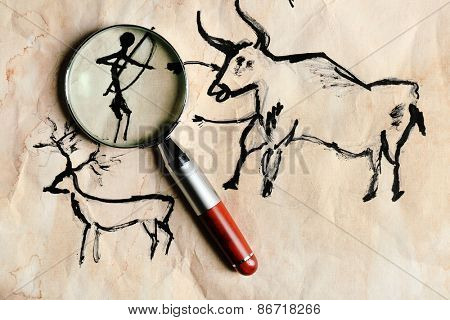 Rock paintings with magnifier on paper close up