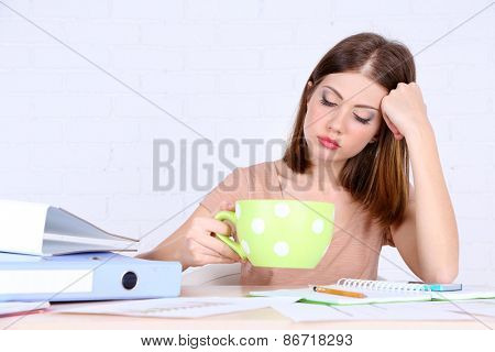 Beautiful girl sitting at table with large cup