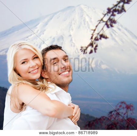vacation, travel, honeymoon, people and tourism concept - happy couple having fun over japan mountains background