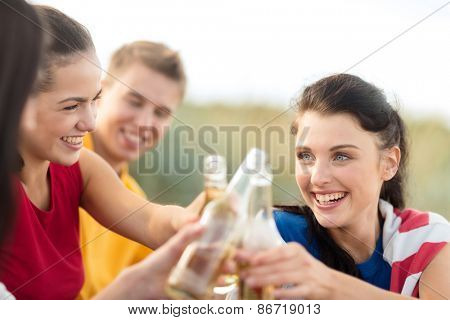 summer holidays, vacation, people and party concept - group of happy friends having fun and drinking beer on beach