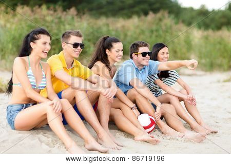 summer holidays, sport, leisure, gesture and people concept - group of happy friends sitting on beach with ball and pointing finger