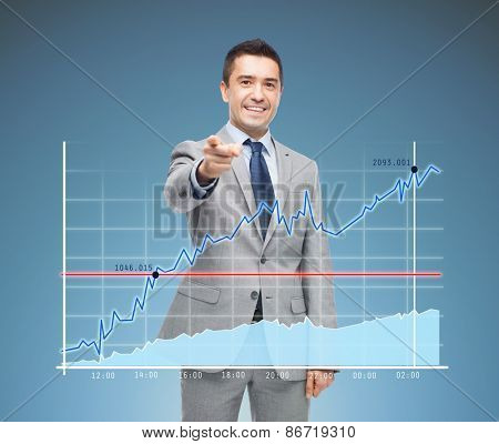business, people and office concept - happy smiling businessman in suit pointing at you over blue background and chart