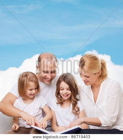 family, childhood, dream and people - smiling mother, father and little girls reading book over blue sky and cloud background
