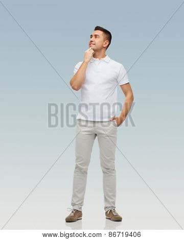 happiness and people concept - smiling man with hands in pockets looking up over gray background