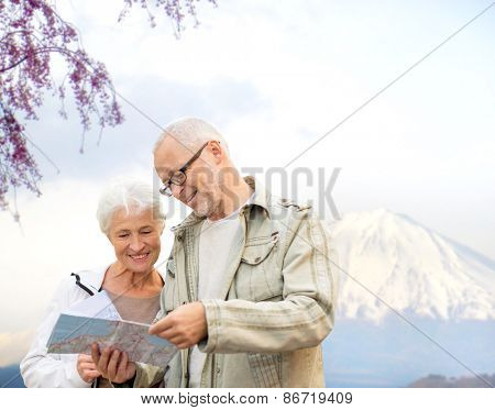 family, age, tourism, travel and people concept - senior couple with map and city guide over japan mountains background