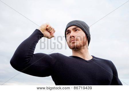 Cool handsome guy with strong arms at outside