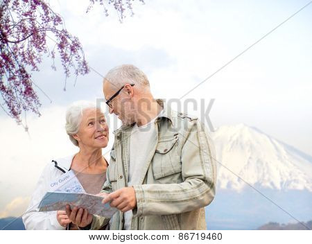 family, age, tourism, travel and people concept - senior couple with map and city guide talking over japan mountains background