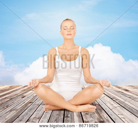 people, relaxation and health concept - woman in underwear meditating in yoga lotus pose