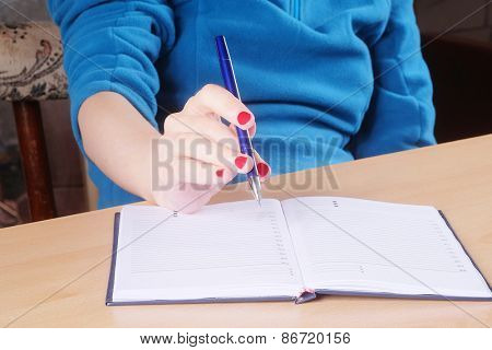 Female hand with pen and notebook