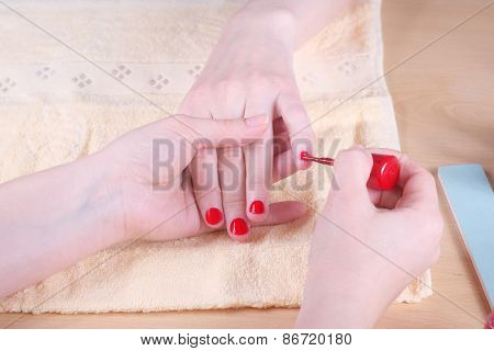 Manicurist doing manicure client painting nails with red nail polish in salon on yellow towel