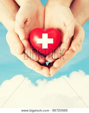 family health, charity and medicine concept - male and female hands holding red heart with cross sign