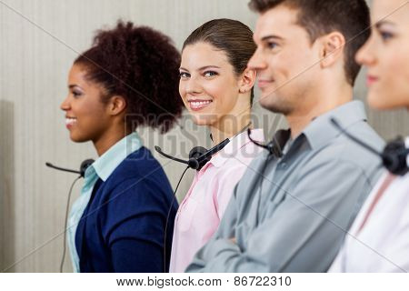 Portrait of confident female customer service representative standing with colleague at call center