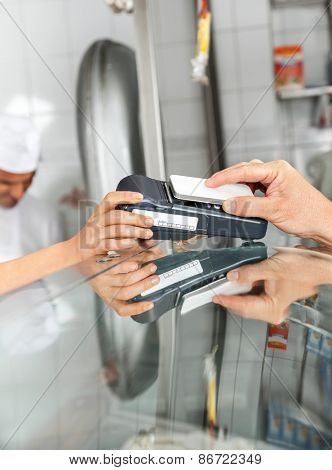 Cropped image of male customer paying through smartphone at butcher's shop