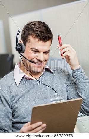 Smiling customer service representative holding clipboard and pen in office