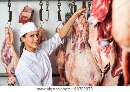 Portrait of mid adult female butcher hanging meat in butchery