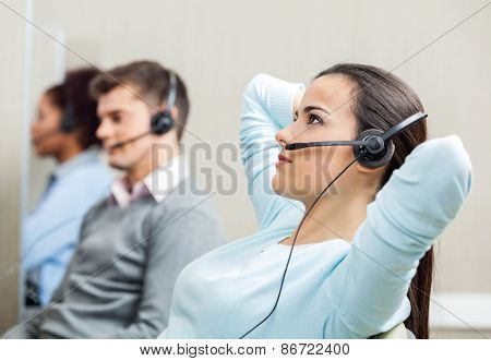 Relaxed female customer service representative wearing headset with colleagues in background at call center