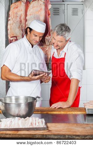 Multiethnic male butchers using tablet computer together in butchery