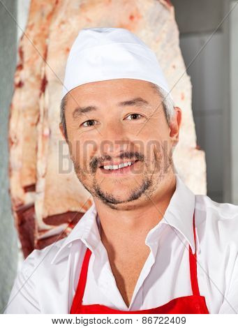 Portrait of confident mature male butcher smiling in butchery
